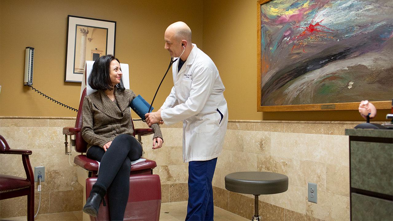 Dr. Amato taking patient's blood pressure