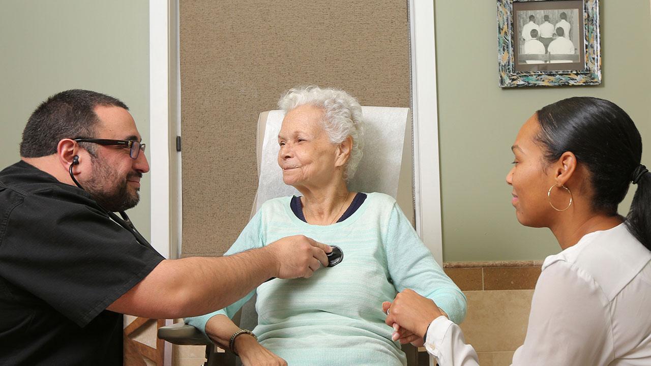 Dr. Di Giorgio listens to a patient's heartbeat